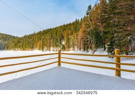 Fence On The Wooden Pier On The Lake. Wonderful Sunny Weather In Winter. Frozen Lake Synevyr Covered