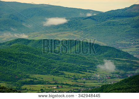 Clouds Rising Above The Hills. Mountainous Countryside Of Carpathians. Fog Evaporate From The Green
