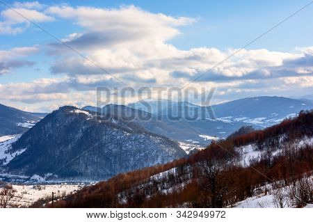 Mountainous Rural Landscape On A Sunny Winter Day. Snow Covered Fields On Hills. Village In The Dist