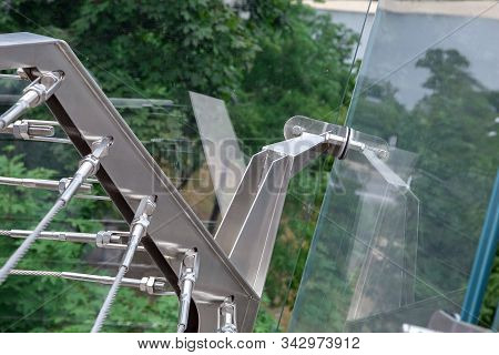 A Corner Of A Glass Bridge With Tension Steel Cables And A Cable Tensioner With Thread Close Up.