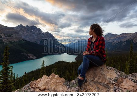 Adventurous Girl Sitting On The Edge Of A Cliff Overlooking The Beautiful Canadian Rockies And Peyto