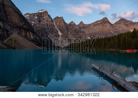 Beautiful View Of An Iconic Famous Place, Moraine Lake, During A Vibrant Summer Sunrise. Located In