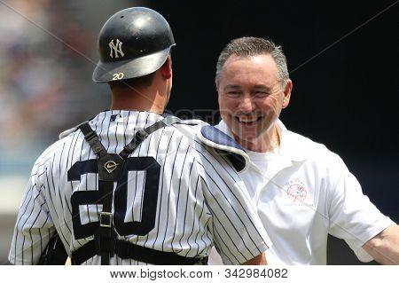 BRONX, NY - JUN 26: New York Yankees trainer Geno Monahan (R) and designated hitter Jorge Posada (20) shake hands during Yankees Old Timer's Day pregame ceremonies on June 26, 2011 at Yankee Stadium.