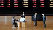Miniature figure business people or Stock Trader looking at Blur Price Stock Ticker board for Graph Analysis poster