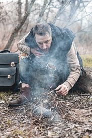A Stock Photo Of A Man In Nature Sitting By A Small Fire, Warming Himself.
