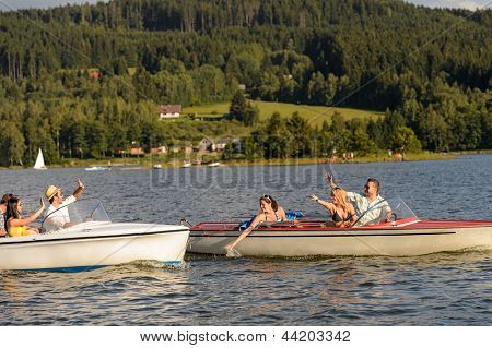 Young friends having fun in motorboats waving and splashing water