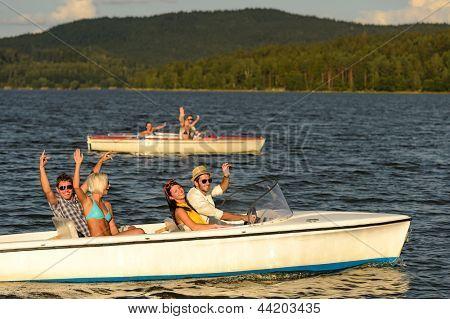 Group of cheerful friends racing with motorboats on river