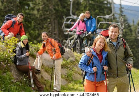 Smiling hikers and cyclists posing peak of the mountain