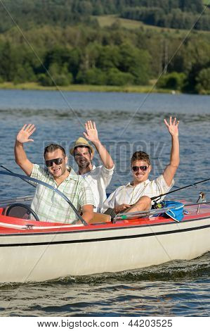 Cheerful young men sitting in motorboat enjoying sunshine