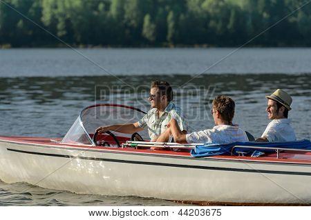 Young men driving speed boat enjoying sunshine