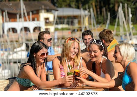 Beautiful women in bikinis toasting with cocktails at beach
