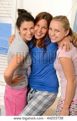 Three teenage girls friends laughing in pajamas together