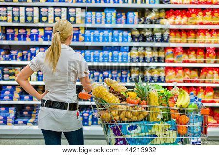 eine Frau ist überfordert mit der großen Auswahl im Supermarkt, beim Einkaufen.