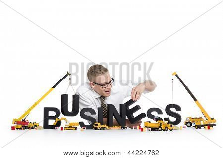 Business start up concept: Smiling businessman building the word business along with construction machines, isolated on white background.