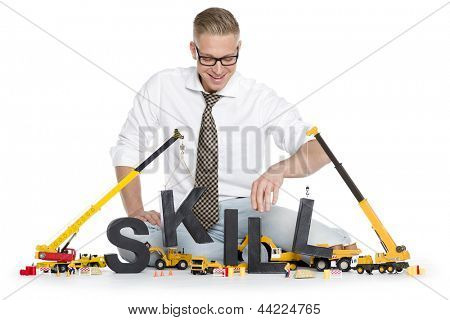 Building up skills concept: Joyful businessman building the word skill along with construction machines, isolated on white background.