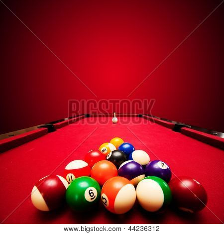Billards pool game. Color balls in triangle, aiming at cue ball. Red cloth table poster