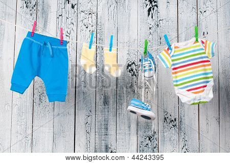 Baby clothes hanging on the clothesline. Child care. poster