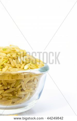 Brown Rice In A Glass Bowl On White Background.
