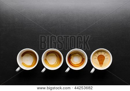 idea. empty and full cups of fresh espresso with bulb sign, view from above