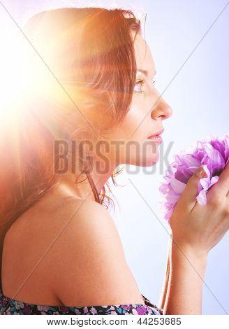 beautiful woman with big flower in sun rays