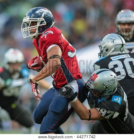 INNSBRUCK, AUSTRIA - JUNE 16 RB DJ Wolfe (#32 Broncos) is tackled by DL Maximilian Pichler (#97 Raiders) on June 16, 2012 in Innsbruck, Austria.