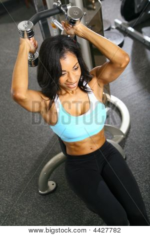 african american woman training or exercising in gym weight lifting for tricep poster