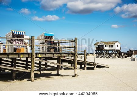 View of building and beach chairs to the sandy beach of St. Peter-Ording at the North Sea in Germany on a sunny day in spring poster