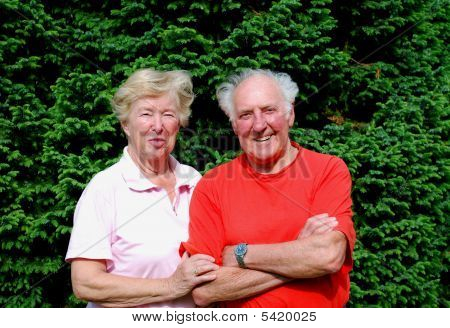 happy senior couple in front of a tree poster
