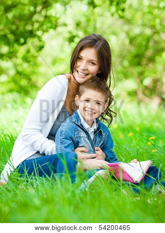 Mom and son with book sitting on green grass in park. Concept of happy family relations and carefree leisure time