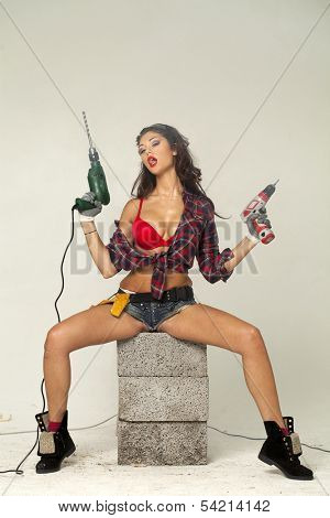 High fashion glamour model in Daisy duke shorts, tool belt, red bra with a screw gun