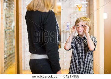Preadolescent boy looking at mother while trying on spectacles in shop