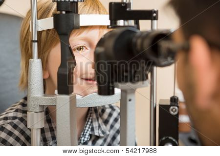 Preadolescent boy's eyes being examined by slit lamp in store poster