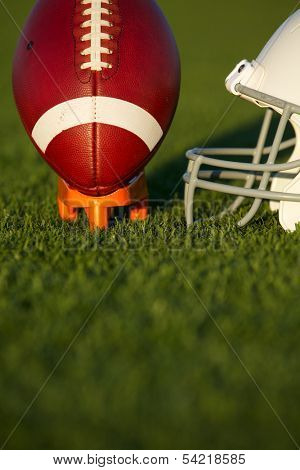 American Football and Helmet on the Field with the Ball Teed Up