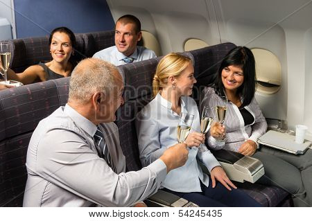 Airplane cabin businesspeople toasting with champagne flight travel passenger