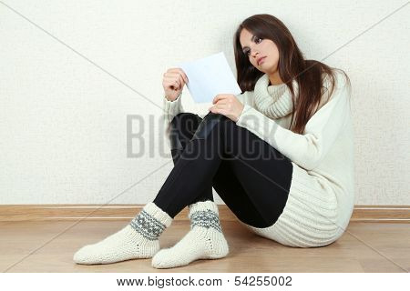 Sad woman sitting on floor near wall