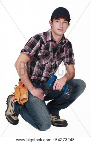Young tradesman holding a rechargeable screwdriver