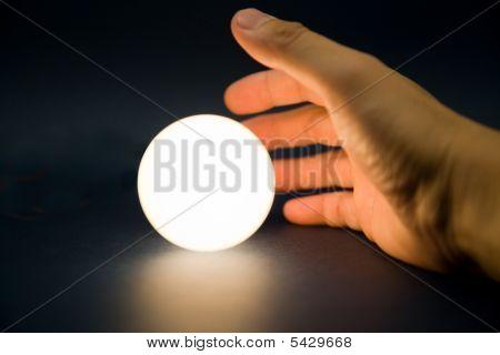 Tocar una bola brillante de la mano