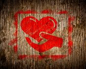 Charity. Red Icon of Heart in the Hand Painted by Stencil on Wood. Grunge Background. poster