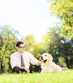Young man sitting on a green grass next to a labrador retriever dog in a park on a sunny day, shot with a tilt and shift lens poster
