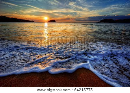 Colorful seaside beach sunrise with distant mountains