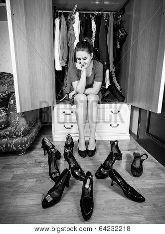 Young Woman Choosing Shoes At Wardrobe