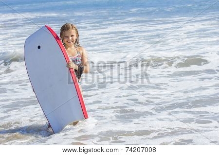 Cute little girl boogie boarding in the ocean