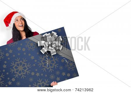 Woman holding a white sign against christmas wrapping paper with bow poster