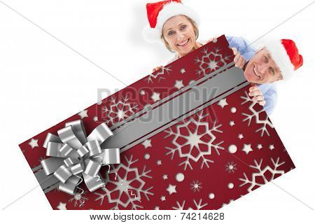 Festive couple showing poster against christmas wrapping paper with bow poster