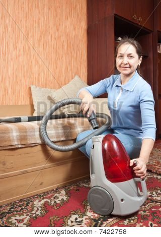 Senior Woman Vacuuming Her Living Room.