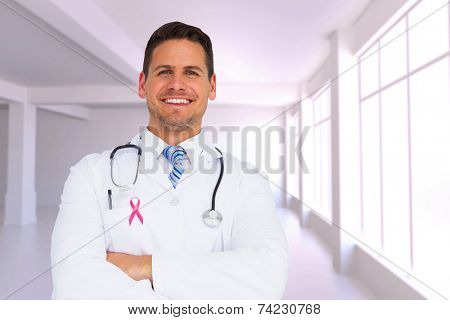 Handsome doctor with arms crossed against white room with windows