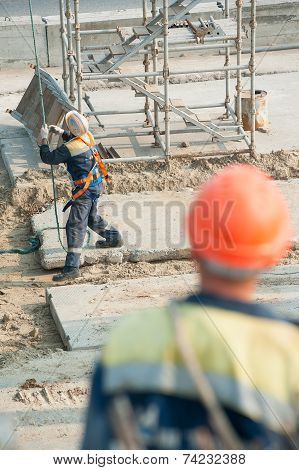 Worker levels provision of plate lifting by crane