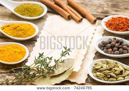 Diversity of Spices on wood background with blank paper sheet. poster