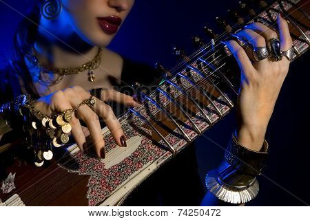 Beautiful young indian woman in traditional clothing with sitar and oriental jewelry. Beautiful bollywood Girl playing the sitar (blue lens effect) poster