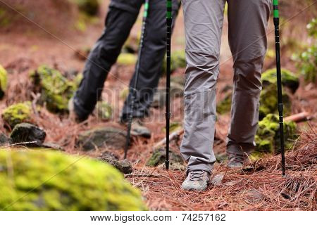Hiking - Hikers walking in forest with hiking sticks on path trail in mountains. Close up of hiking shoes and boots. Man and woman hiking together.